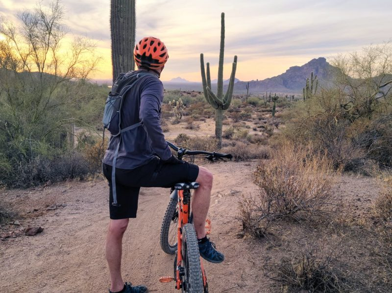 A man leaning on a mountain bike with the Arizona desert in the background