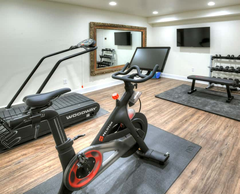 Fitness center with free weights, yoga mats, stationary bike and treadmill