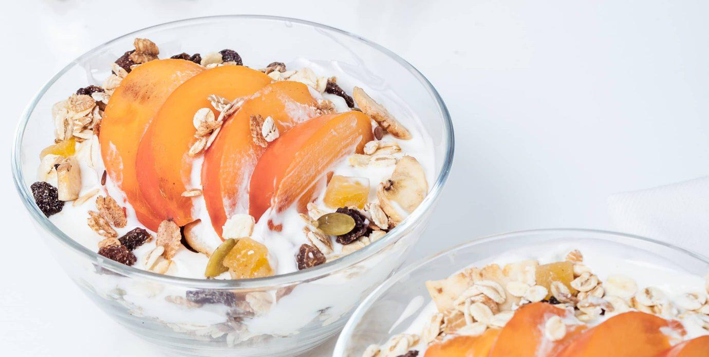 Fresh sliced peaches served with yogurt and granola