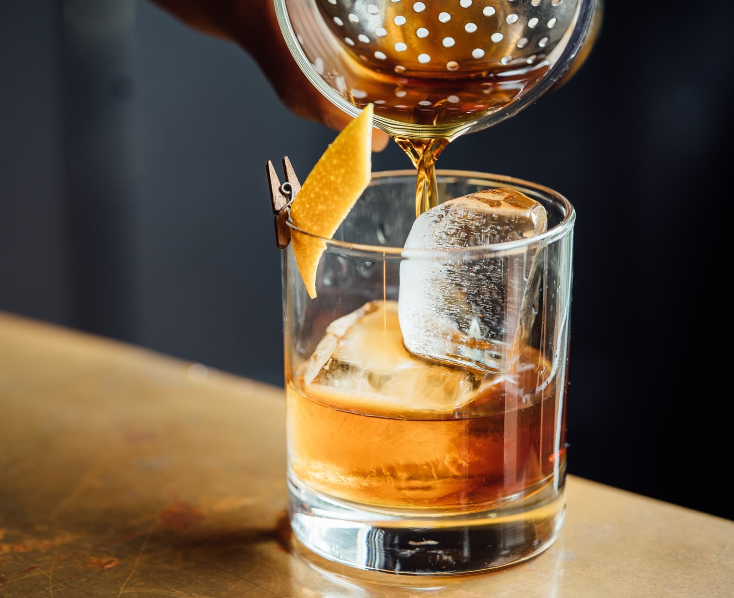 Whiskey pouring into a glass with two large ice cubes